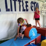 Nora doing an assisted backflip with The Little Gym at Da Vinci Days.