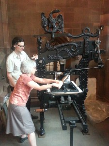 Anita Guerrini working a printing press
