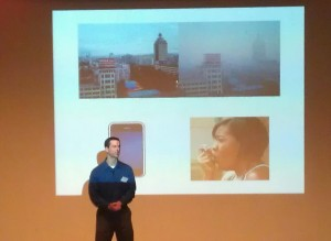 Andy Larkin in front of slide with images of city, person using inhaler.
