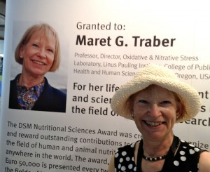 Maret Traber in front of large sign about her work.
