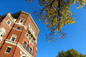 Top of OSU's Weatherford Hall, blue sky and golden leaves