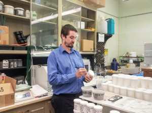 Researcher Delvan Neville labels containers of albacore tuna samples