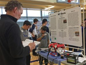 A judge evaluates a display created by the ROV Sharks, a Wasco County 4-H team from The Dalles.