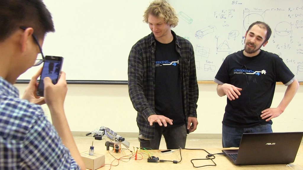 "Ryan Green and Keaton Scheible demonstrate their project, ""Go Go Gadget Claw,"" while teammate, Rattanai Sawaspanich takes a video."