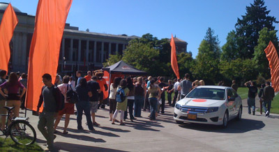Students and staff gather in the MU quad for orange giveaways.
