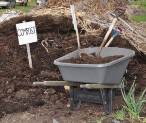 Compost pile with wheelbarrow