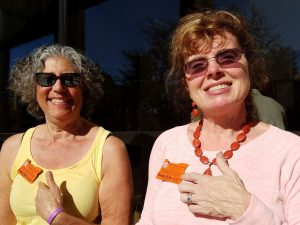 Alice Goldstein and JonMarie Purvis pointing at their OSU Master Gardener badges
