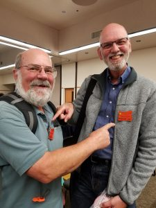 Master Gardeners Marty Zimmer and Dennis Brown point to each other's OSU Master Gardener badge