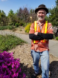 Master Gardener wearing hat and safety vest, smiling waiting to assist customers loading plants from plant sale.