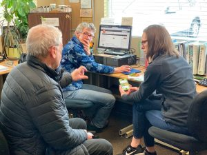 Two Master Gardeners in Master Gardener office talking to a client.