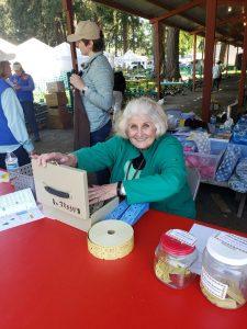 Smiling Master Gardener volunteer at raffle table at Spring Garden Fair.