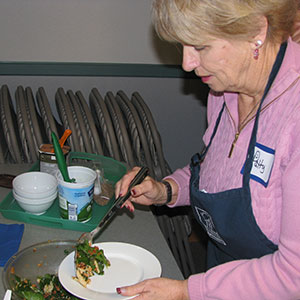 Patty Stark dishes up smoked salmon salad, a recipe she learned in the Nourishing Boomers and Beyond course in Deschutes County. Photo by Glenda Hyde.