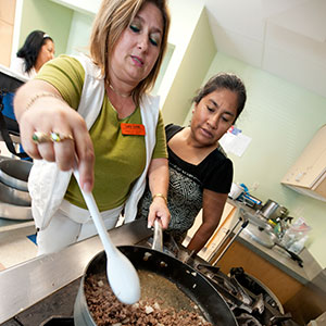 Lucy Lores, an educator with the Oregon State University Extension Service, demonstrates a healthy recipe during an eight-week nutrition education program for Hispanic families in the Portland area. Photo by Lynn Ketchum.
