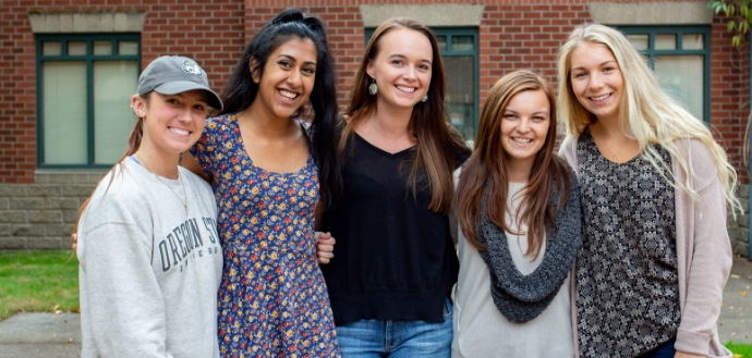 Group of nutrition students smiling in front of a brick building