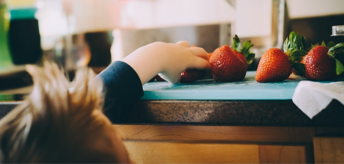 Child grabbing strawberries on a counter