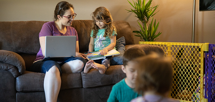 Mother of three works on course work as children play around her