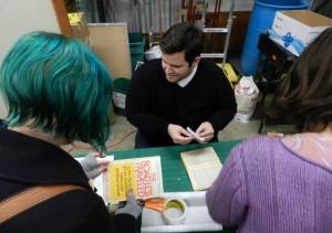 Volunteer Kyle runs a book repair demo. Click to view larger.