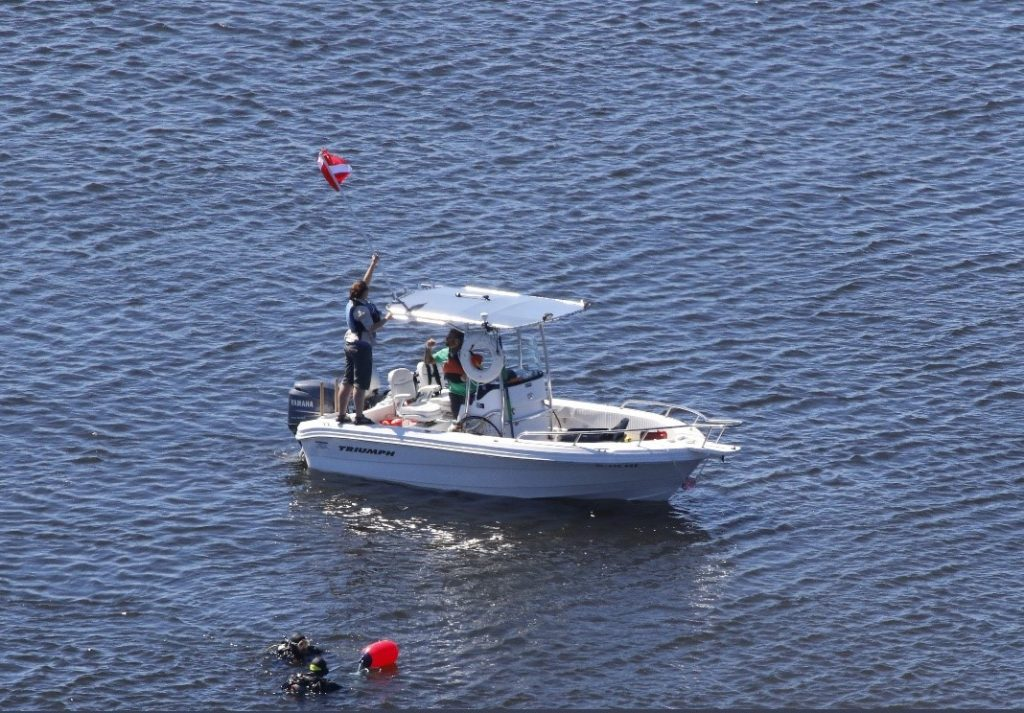 Fig. 8 Equipment rescue team: Aaron Galloway and Taylor Eaton diving, Greg Ryder operating the boat, and Florence on board to direct the GPS location of where the equipment was lost.