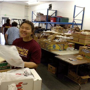 Courtney Kamiya packing boxes during Alternative Spring Break
