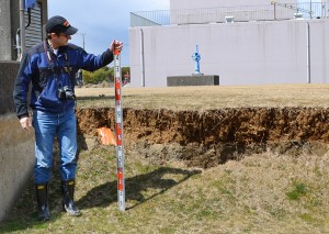 Oregon State University Professor Scott Ashford measures ground upheaval during a visit to Japan following a major earthquake there. (photo courtesy GEER)