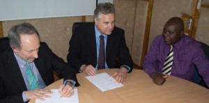 XXXX of the Kenyan meteorological department signs an agreement with John Selker, left, and Nick van de Giesen, middle, to guide installation of TAHMO weather stations in his country. (Photo courtesy of John Selker)