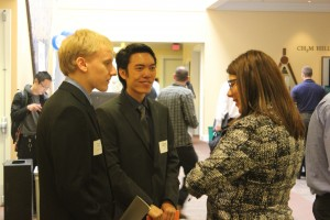 Two students speaking with a recruiter at a career fair