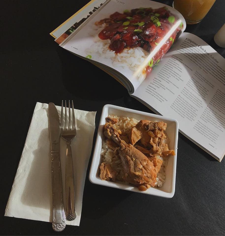 Chicken is in a bowl with rice, a cookbook is open to a page with the recipe for it.