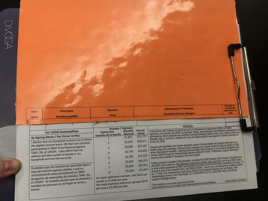 A form with text explaining income eligibility and non discrimination policy is obscured by an orange piece of paper.