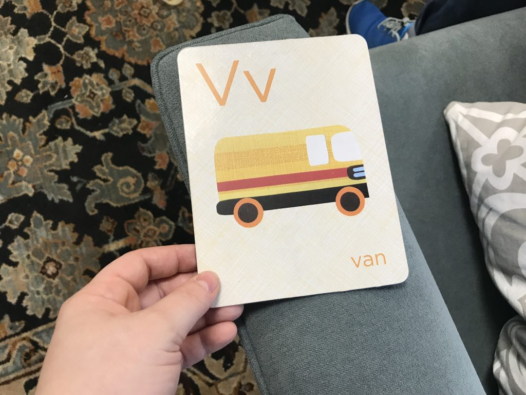 An illustration of a van is on a card, with a capital V and a lowercase v on it. The card itself sits on the arm of a couch.