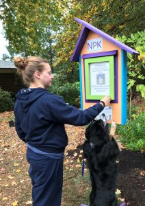 A young woman and a dog check out a Neighborhood Planters Kiosk