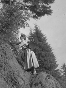 Mrs. Irene Finley climbing up a rock face with photography equipment on her back. OHS Research Library, Org. Lot 369, Finley A1327.