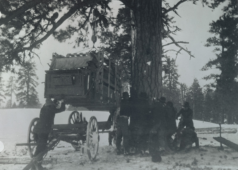 A group of unidentified men working to lift an elk crate from the wagon base with a pulley to transfer to sled runners after snow became too deep to continue with the wagons. Wallowa Mountains, Oregon, 1912. OHS Research Library, Org. Lot 369, Finley B0484.