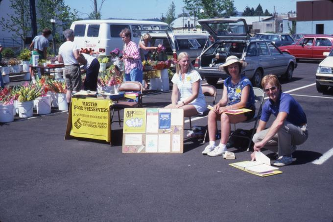 Benton County Extension service Master Food Preservers provide information at the Corvallis Wednesday Farmers Market in the parking lot east of the Avery Square building, 1986. From P062:Series VII