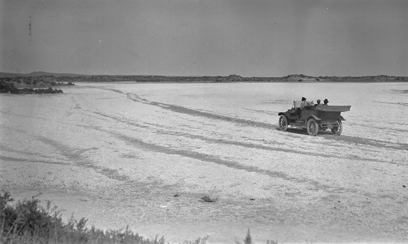 Three men in a touring car driving across Alkali Flat on their way to inspect an egret colony near Silver Lake, Oregon, 1912. OHS Research Library, Org. Lot 369, Finley B0160.