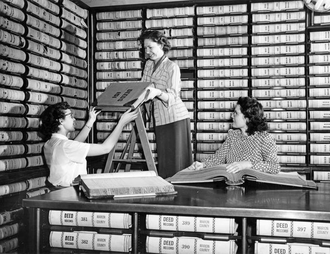 Women refiling deed books at the Marion County Courthouse, circa 1950. Recorder's office staff in the vault. From left to right: Romona Evans, Salem; Virginia Gritton, Salem; and Irene Johnson, Salem. P218 SG4 Series II