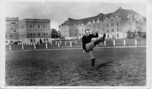 Football player punting the football with Waldo Hall and Langton Hall in the background.