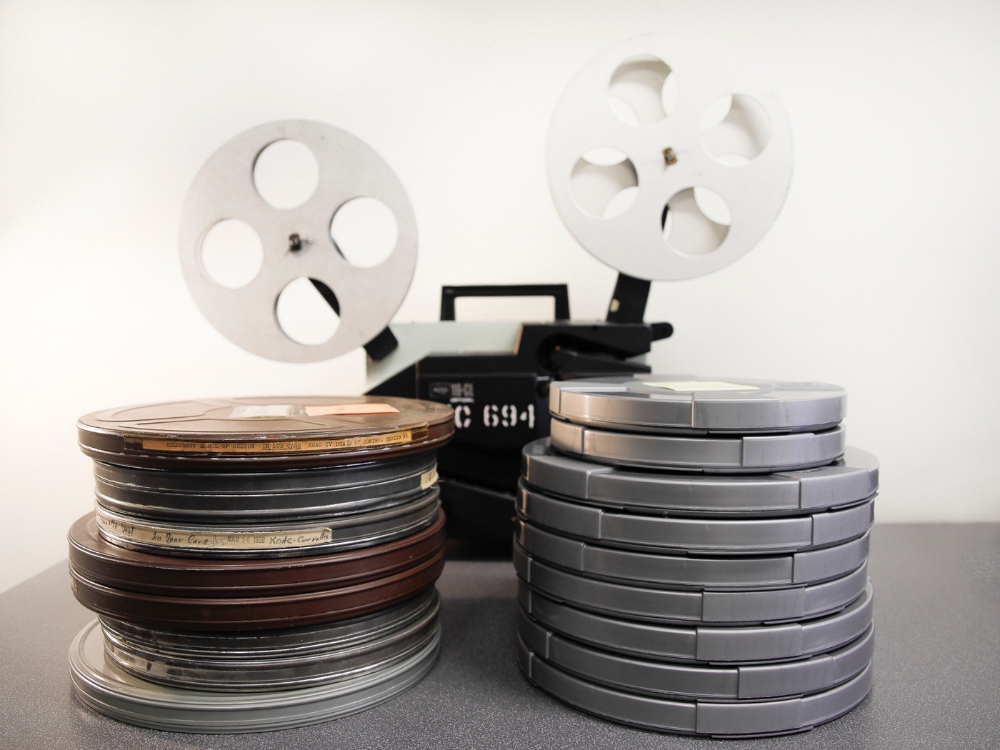 Some original metal cans piled up; the same pile of films once rehoused to polypropylene cans.