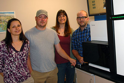 Natalia Shulzhenko, Brendan Jeffrey, Aimee Reed, and Tim Putman standing next to the Illumina Hiseq 2000 used for genome sequencing at the OSU Center for Genome Research and Biocomputing .