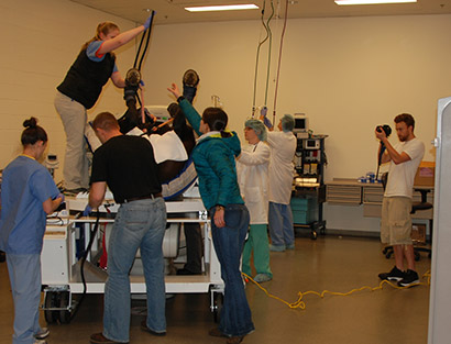 Videographer Jake Fagan films the large animal hospital team  getting a horse ready for a CT scan.
