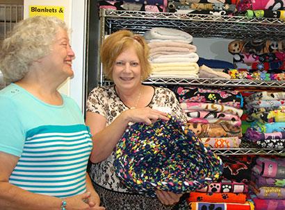 Volunteer coordinator Tammy Barr holds a crocheted fleece pet bed made by Dianne Ostergaard.