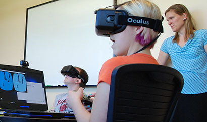 Dr. Sarah Nemanic observes students testing virtual reality goggles used with a teaching tutorial.