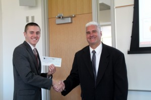 Blake Hendricks accepts a check from D.A. Davidson & Co.'s Rich Fisher for OSIG's first place win in the Portfolio Competition.