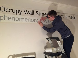 Jeremy Banka affixes lettering to the wall of the display area at the Autzen House.
