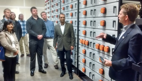 Kevin Whitener of Portland General Electric, right, addresses the tour group by the Beaver-colored bank of batteries in Salem. Center is tour organizer Pradeep Kumar of the Portland chapter of the Society of Information Management.