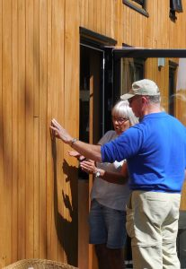 Turid Svenneby discusses weathering of oiled oak siding with trour member Claude Rowley.