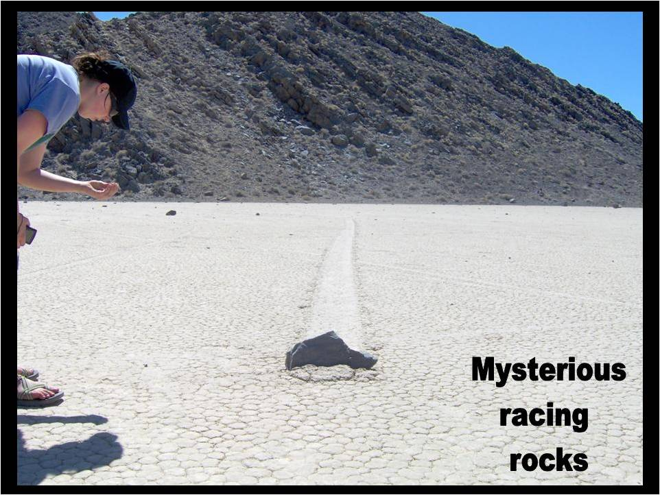 At Racetrack Playa -- this photo beautifully illustrates the process that has confounded geologists for years. The cliffs of tilted dolomite in the background have shed many rocks that fall down onto the playa floor. During intense rainstorms, these rocks slide across the playa aided either by wind and wet mud, a thin ice sheet or possibly both. Wind seems to be the favored mechanism at this point, but no one knows for sure because the action has never been observed. Note the dirt in front of the rock, which appears to have been scraped into a pile