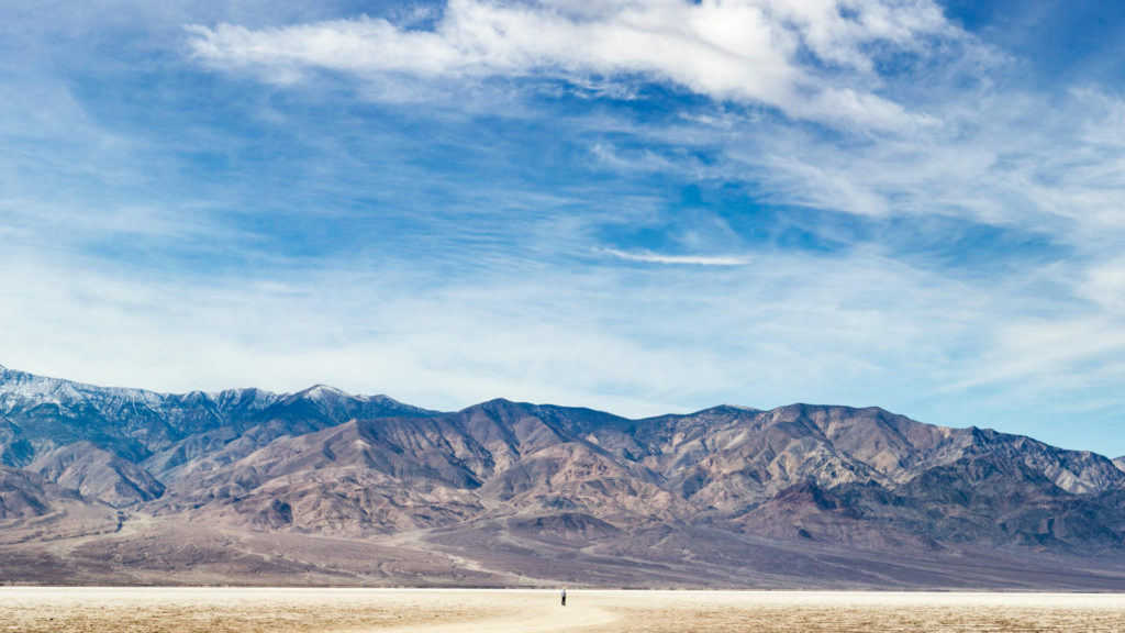 Panoramic photo of a lone person standing in the vast landscape of Bad Water Basin in Death Valley National Park in California.