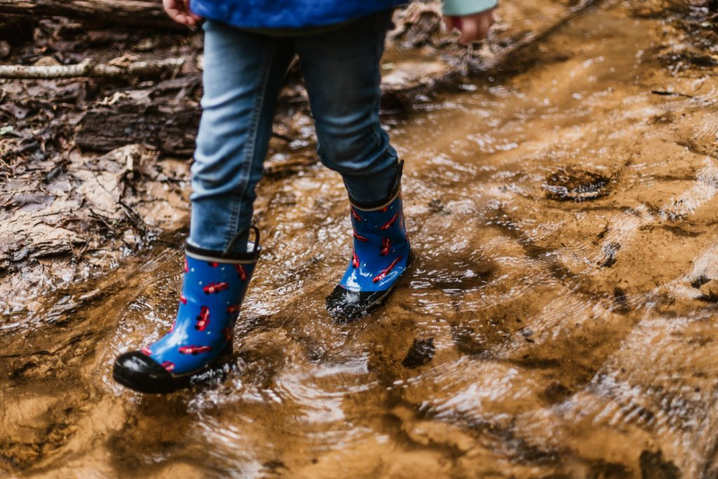 child in mud puddle in rain boots