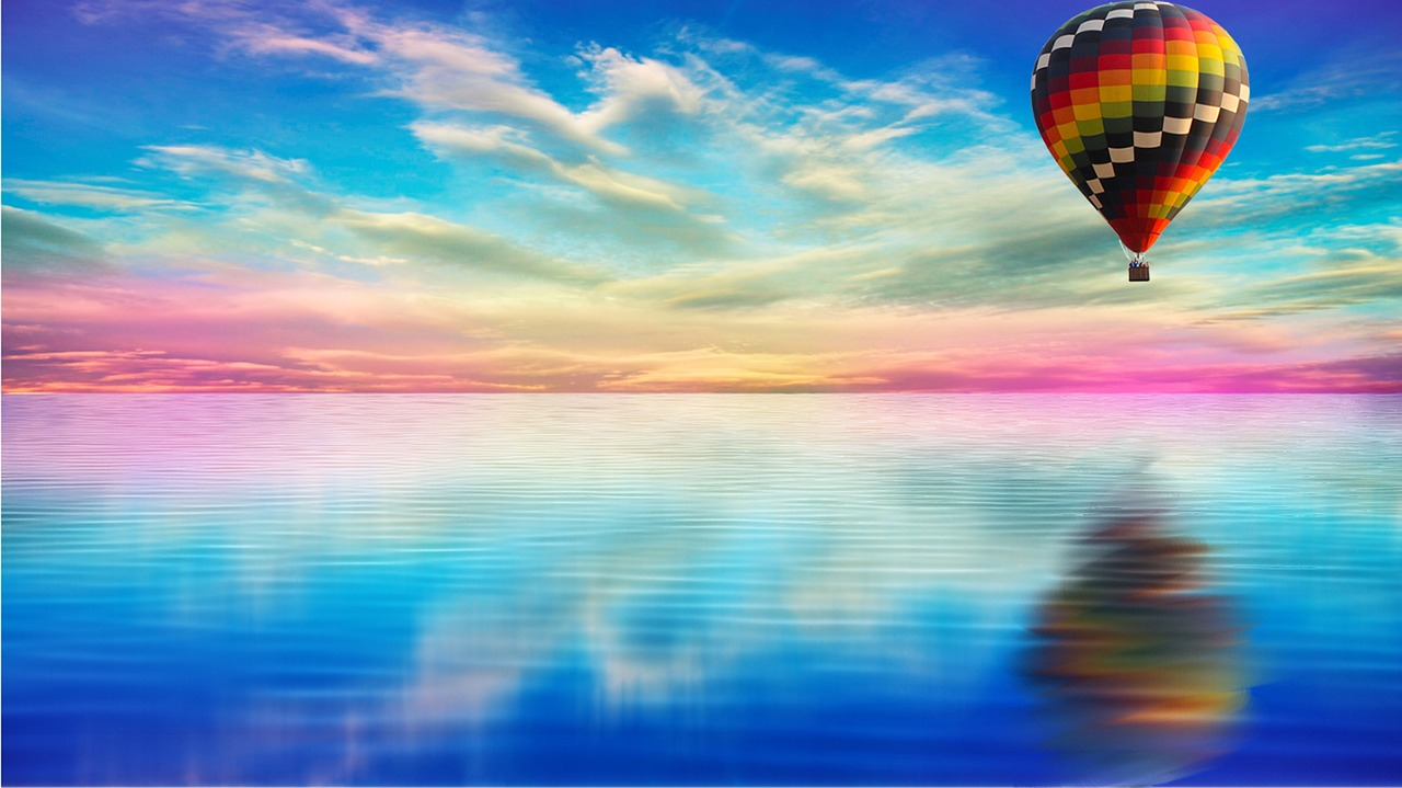 reflection of hot air balloon over water