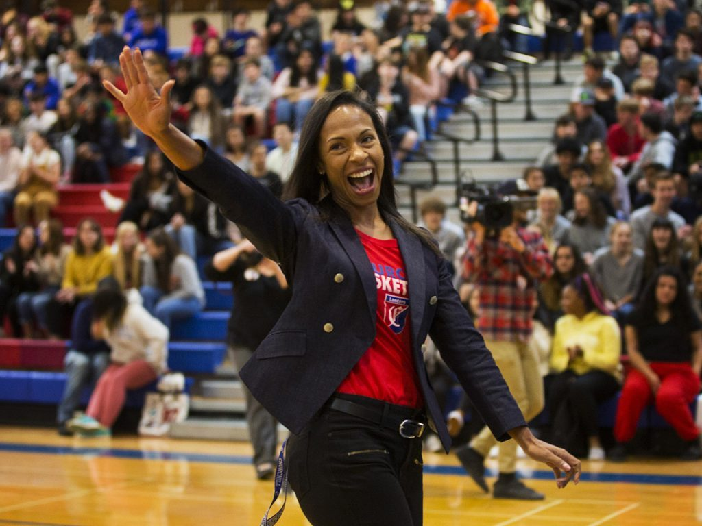 Keri Pilgrim-Ricker smiling and waving as she addresses a gymnasium of students.